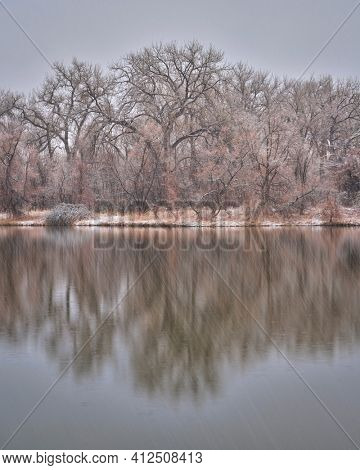 heavy snowstorm over small lake in northern Colorado, one of natural areas along the Poudre River  in Fort Collins,