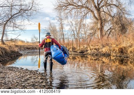 senior male paddler is launching his inflatable packraft on a river in early spring spring - Poudre River in northern Colorado