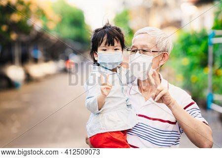 Grandfather Carried Granddaughter For Walk On Road. Kids And Old People Put Up Hands With Two Finger