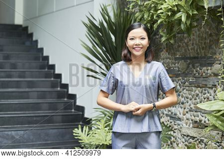 Portrait Of Smiling Vietnamese Spa Salon Manager Standing At Entrance And Welcoming Clients