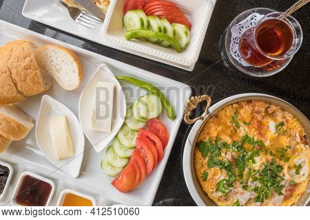 Delicious traditional turkish breakfast with menemen, cheese, bread and glass of turkish tea on the table. Top view.
