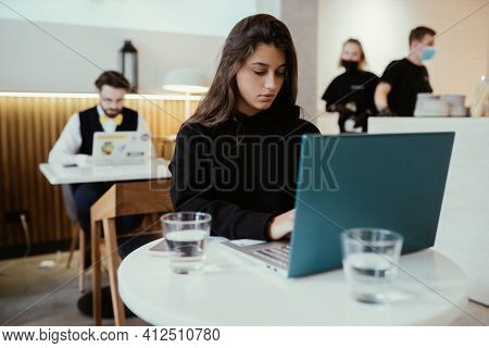 Portrait Of Female Student Using Net-book While Sitting In Cafe