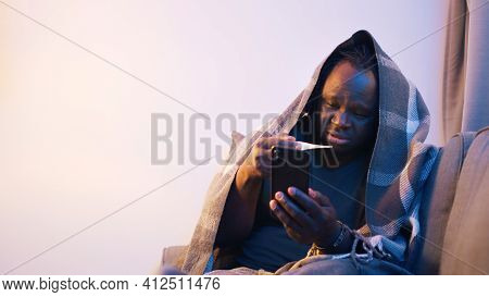 Online Health Care. Sick Man Wrapped In Blanket Measuring Temperature And Seeking Distance Medical H