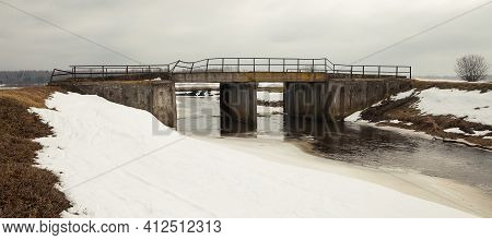 River In Early Spring On The Bank Of Snow. Old Bridge Over The River. The Snow Melts With The Arriva