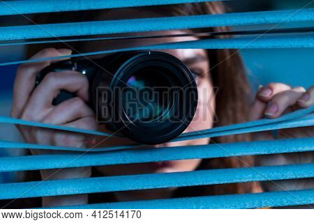 Young paparazzi woman with photo camera in hand looks out the window through the blinds