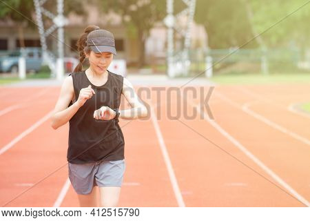 Portrait Of Young Athlete Runner Woman Running In The Running Track And She Looking To Her Smart Wat