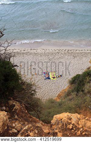 Sant Tomas, Menorca / Spain - June 25, 2016: Tourist At Binigaus Beach With Flowers, Sant Tomas, Men