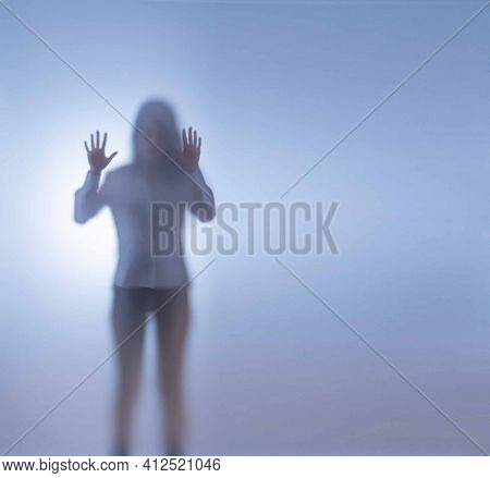 A young woman stands behind frosted glass. The concept of kidnapping and keeping them in captivity