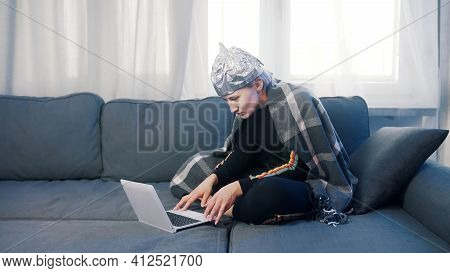 Fearful Young Woman With Aluminum Hat Browsing Social Media. Conspiracy Theory About 5g Network Dest