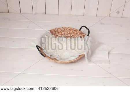 Wicker Basket On A Wooden Background. Photo Zone For Taking Pictures Of A Newborn Baby. White Fur, W