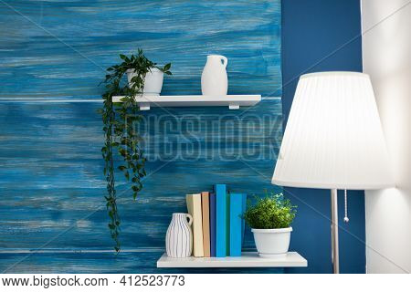Green Flowers On White Shelf In Blue Room. Cozy Home Living Room With Nobody In It With Beautiful In