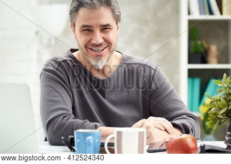 Portrait of happy man at home sitting at desk, working, looking at camera. Happy smile, grey hair, beard. Portrait of mature age, middle age, mid adult man in 50s.