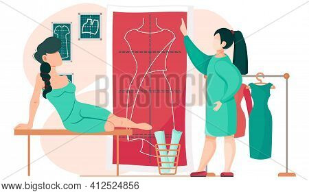 Seamstress Points To Poster With Pattern. Girl Sitting On Table Looks At Design Of Unfinished Dress