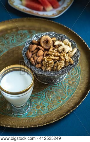 Bowl of assorted dry fruits containing healthy and nutritious almonds, digs, cashew and walnuts. Glass of milk served in a tray with mixed nuts- a power snack.
