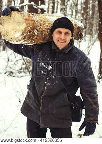 Logger Harvesting Wood For Firewood In Forest