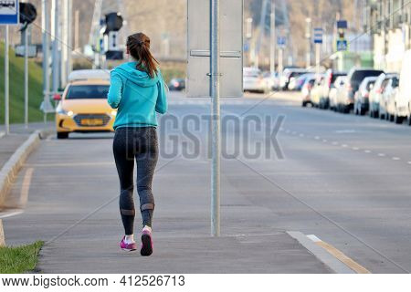 Slim Girl Running On The Sidewalk Along The City Street, Rear View. Alone Runner, Concept Of Workout