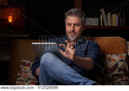 Man sitting on couch at home with tablet computer. Businessman working in home office. Portrait of mature age, middle age, mid adult man, bearded, authentic look.