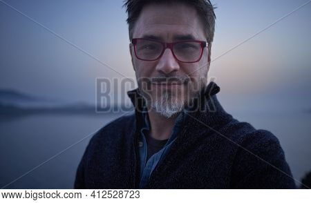 Portrait of mid adult man in front of cold nordic landscape. Portrait of mature age, middle age, mid adult man in 50s, happy smile.