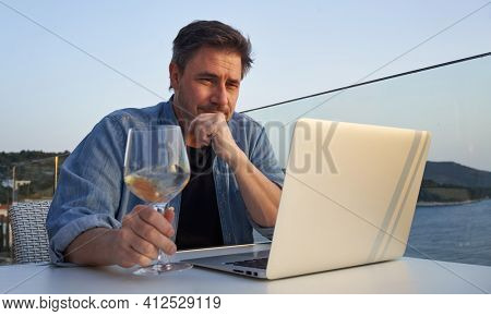 Businessman on vacation at sea working with laptop, drinking wine. Home office, online wine tasting, tele working, video chat. Escape, freedom, getaway .