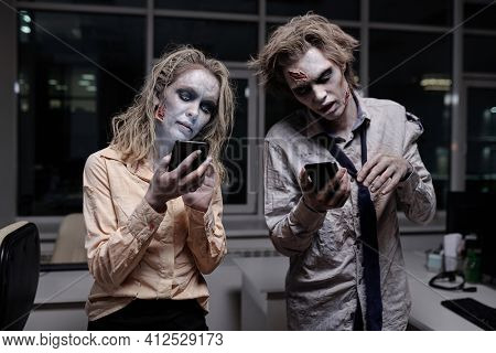 Dead and spooky businesspeople with zombie greasepaint on their faces and hands using smartphones