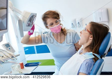 Female dentist treating patient in dentist's office.