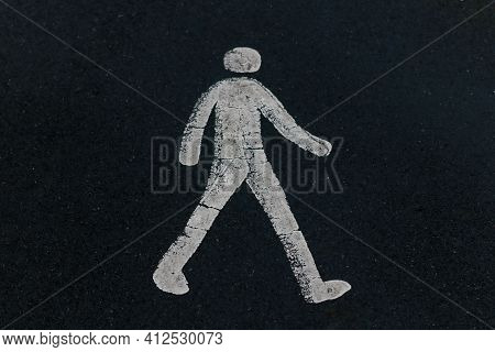 A White Painted Pedestrian Sign On Black Tarmac On A Road Surface In The Uk