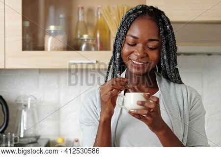 Portrait Of Happy Smiling Young Black Woman Mixing Milk And Sugar In Cup Of Morning Coffee