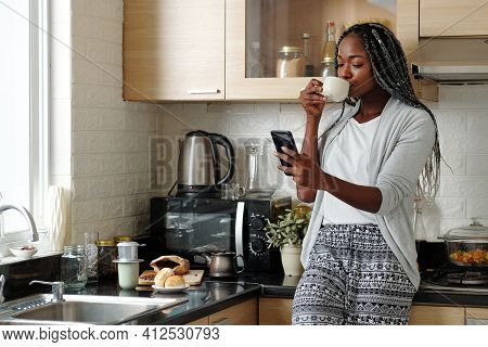 Pretty Young Black Woman Standing At Kitchen Counter, Drinking Morning Coffee And Reading Text Messa