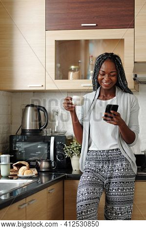 Cheerful Young Black Woman In Loungewear Drinking Cup Of Morning Coffee In Her Kitchen And Laughing