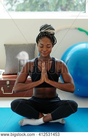 Smiling Calm Young Black Woman Sitting On Yoga Mat In Lotus Position And Meditating With Hands In Na