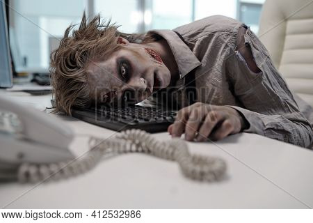 Dead businessman with zombie body painting keeping head on computer keyboard after working