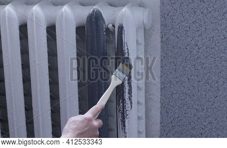 A Hand With A Long Narrow Brush Paints A White Radiator In A Dark Gray In A Room With Gray Wall Deco