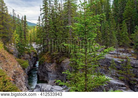 Maligne Canyon is the most unusual and interesting gorge in the Canadian Rockies. Travel to the Rocky Mountains. Cool cloudy day. The sheer canyon walls and the seething icy water below.