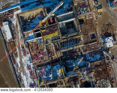 Top view of industrial machinery and building under construction located in enclosure in snowy outskirts