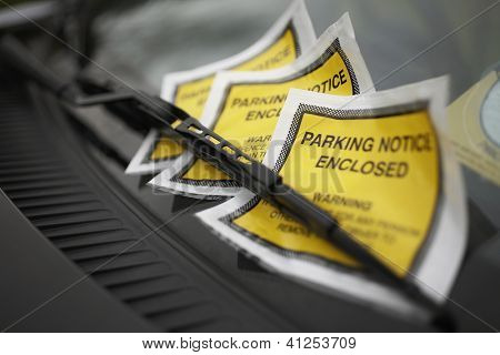 Close up of parking ticket placed under windshield wiper of a car