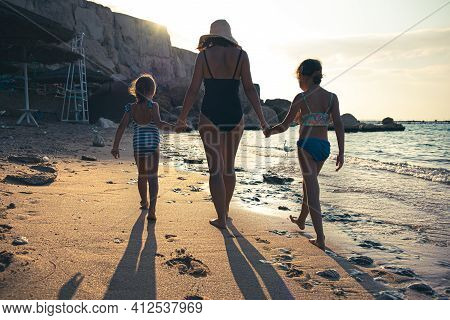 Mom And Two Little Daughters Walk Along The Seashore In Swimsuits, Holding Hands. Vee From The Back.