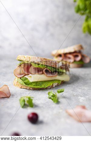 Vertical View Of A Sandwich Made Of Crispy Bread, Dried, Smoked Sausage, Cheddar, Lettuce. Breakfast