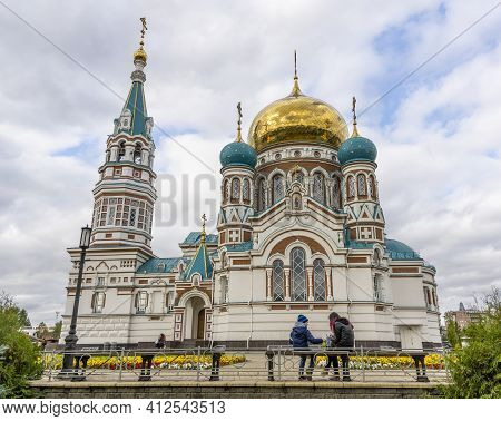 Omsk, Russia - September 13, 2019: Dormition Cathedral In Omsk With Two People Or Children Sitting I