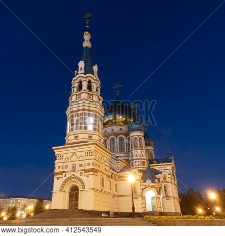 Omsk, Russia - September 13, 2019: Dormition Cathedral In Omsk At Night With Golden Roof And Blue Sk