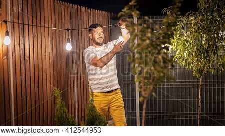 Party Time In Backyard With Happy Millennial Man Hanging String Lights In Trees - Weekend Night Mood