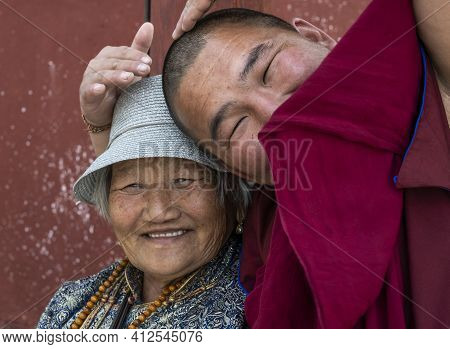 Mörön, Mongolia - August 17, 2019: Buddhist Monk Wit Red Habit Clothes In Buddhist Temple With Woman