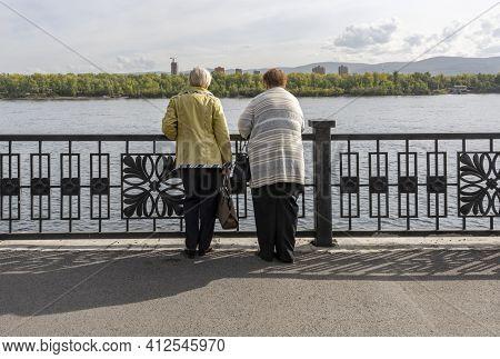 Krasnoyarsk, Russia - September 9, 2019: Two Woman  Waiting At The Balustrade At The River Yenisej I