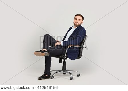 Young Businessman Sitting In Comfortable Office Chair On Grey Background