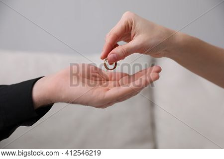 Woman Giving Wedding Ring To Her Husband Indoors, Closeup. Divorce Concept