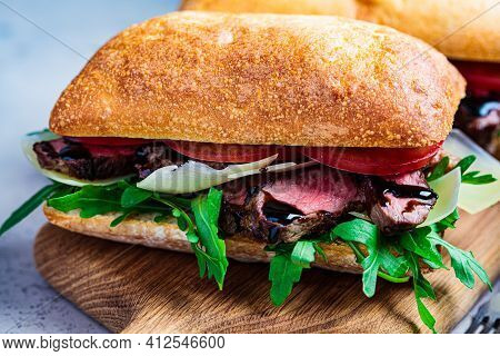 Beef Steak Sandwich With Arugula, Tomato And Parmesan On A Wooden Board. Comfort Food Concept.