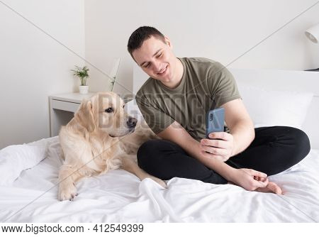 A Young Man Holds A Mobile Phone While Sitting On A Bed With A Dog And Caresses His Pet. Portrait Of