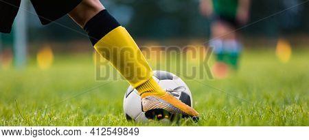 Footballer Kicking Ball Moment. Closeup Of Soccer Players Leg Moving Toward Soccer Ball. Athlete In
