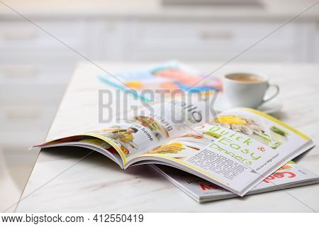 Culinary Magazines And Cup Of Coffee On Table In Kitchen