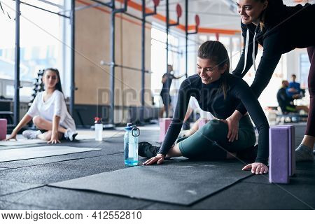 Helpful Instructor Guiding Women Experience At The Gym