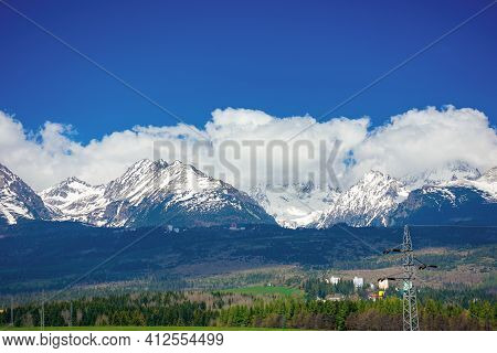 High Tatra Mountain Ridge In Springtime. Cloud Above The Snow Capped Rocky Peaks. Beautiful Sunny We